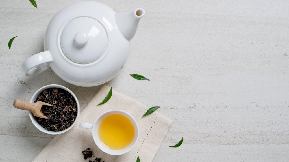 A cup of green tea with tea leaves and a tea pot (antioxidant)