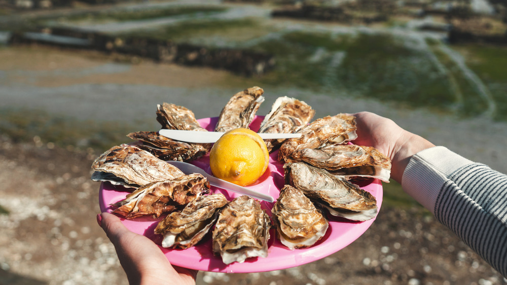 person carrying a platter of oysters
