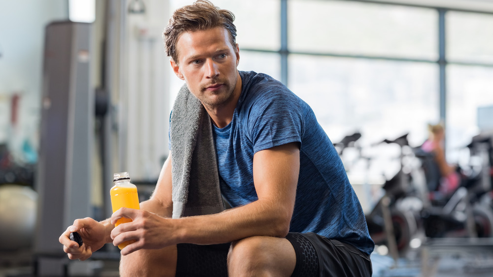 man at gym with bottle of juice