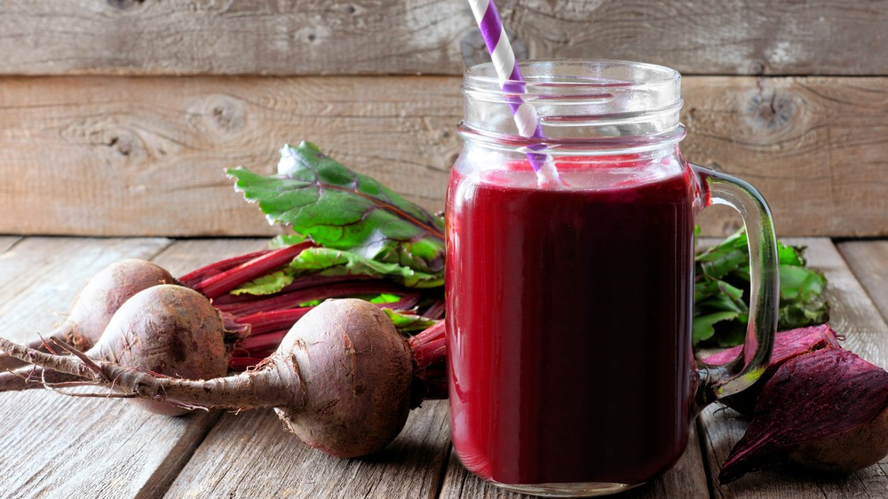 glass of beet juice surrounded by beets