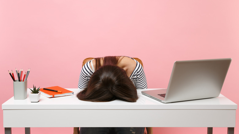 tired woman with head on desk
