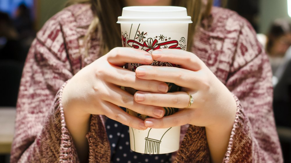 A woman holding a hot coffee beverage