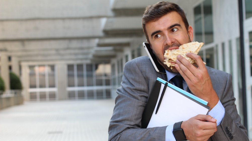 A man eating a sandwich while on his phone, walking