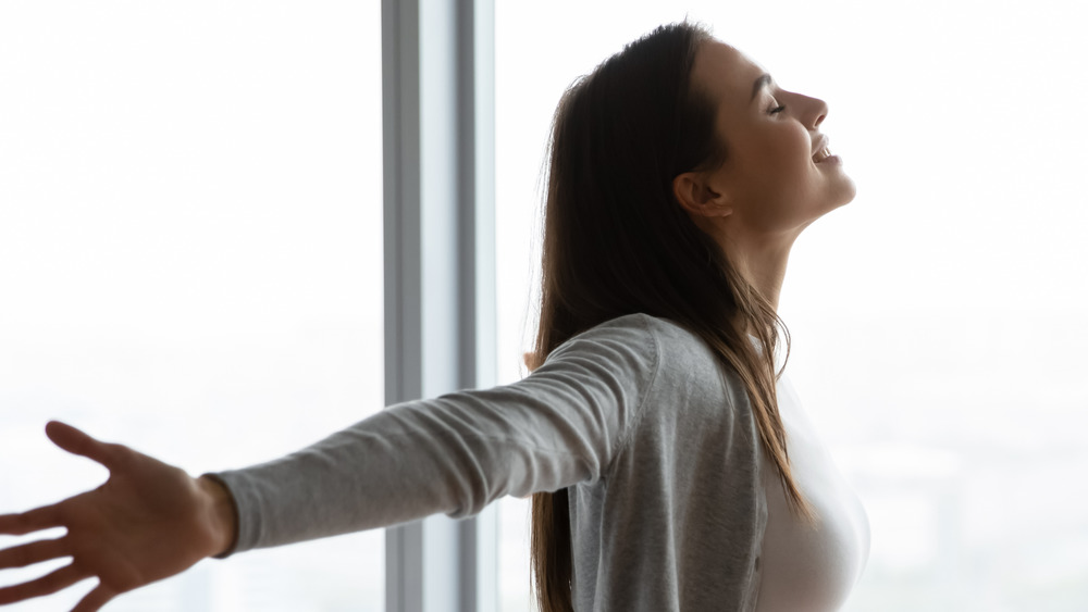Woman with outstretched arms by a window