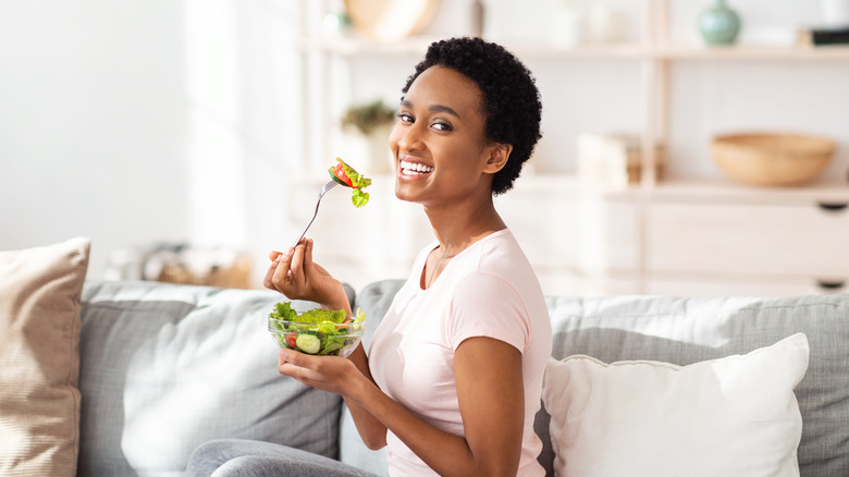 Woman smiling on the couch eating a salad