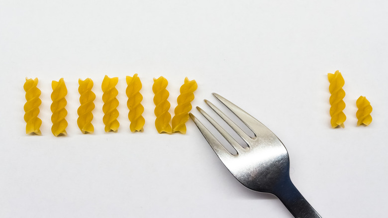 Pieces of pasta being counted with a fork