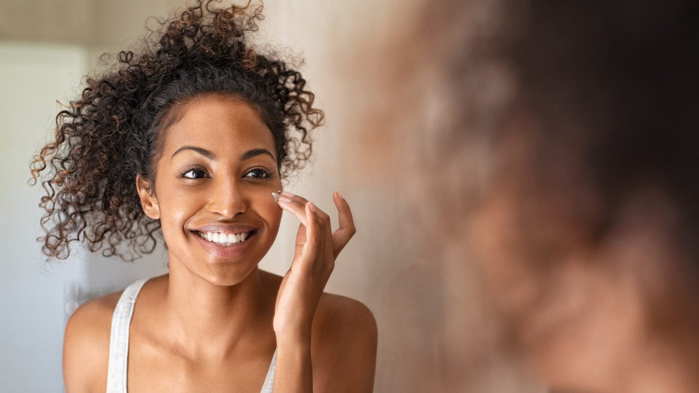 Woman moisturizing her face.