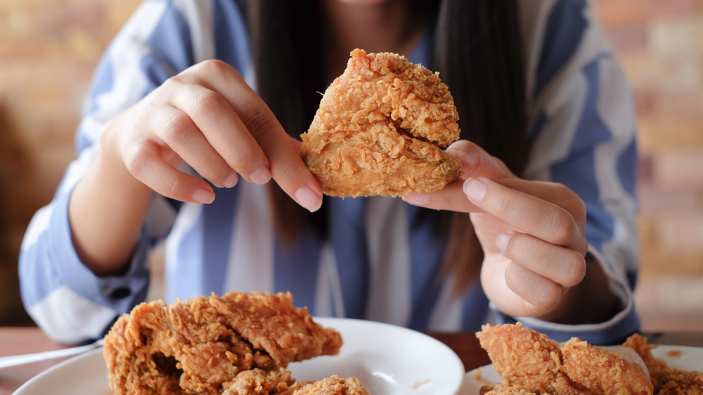 woman holding fried chicken