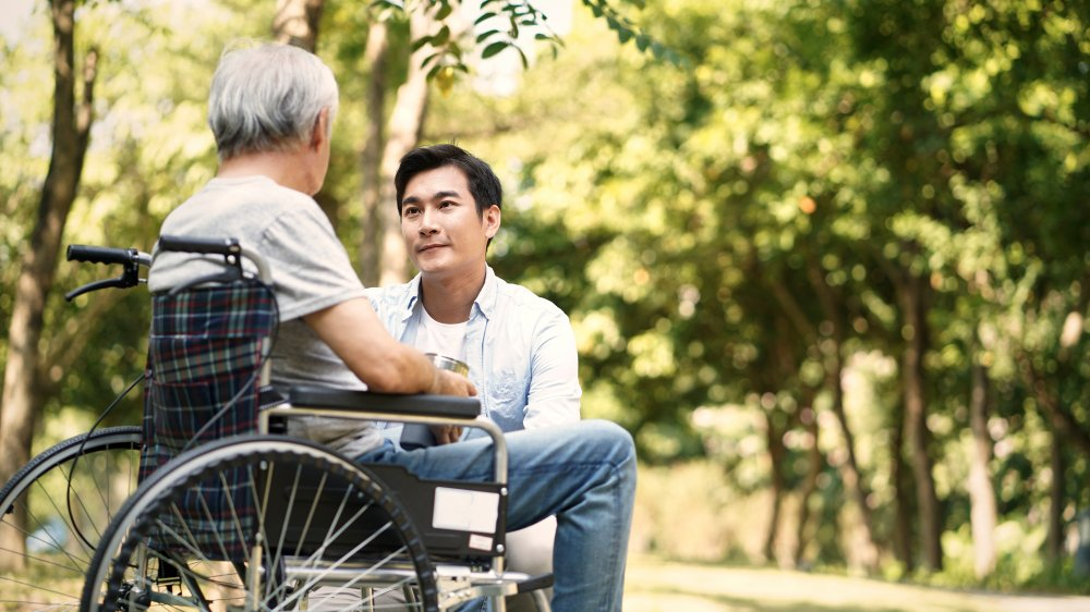 younger man talking to older man in wheelchair
