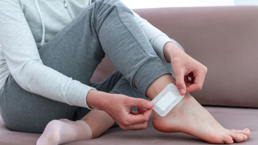 woman putting Band-Aid on ankle